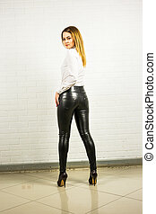 standing beautiful young lady with leather pants.