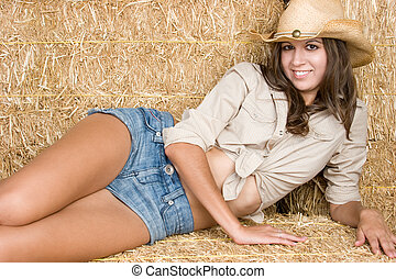 Cowgirl in Hay - Smiling cowgirl laying in hay