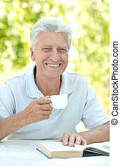 Handsome older man sitting at a table at home on the veranda...