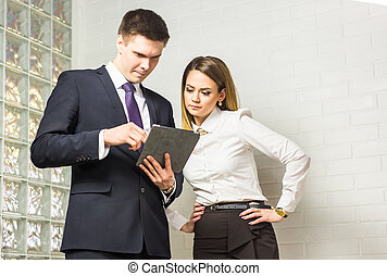 Business people discussing ideas at meeting using tablet in the office