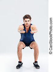 Handsome young sportsman doing squats over white background