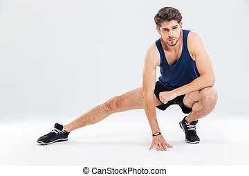 Attractive young male athlete stretching his legs over white...