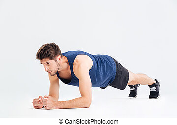 Focused handsome young sportsman doing plank core exercise...