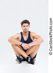 Portrait of confident young sportsman sitting with legs...