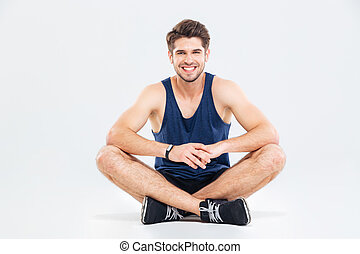 Cheerful young man athlete sitting with legs crossed