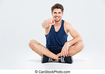 Cheerful sportsman sitting with legs crossed and pointing on...