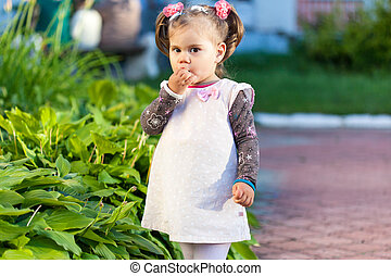 Girl is eating candy - Little child girl in dress is eating...