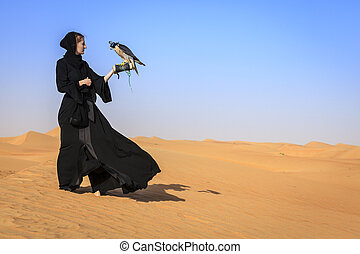 Woman with Peregrine Falcon - Young woman in abaya with...