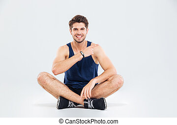 Smiling fitness man sitting with legs crossed and pointing...
