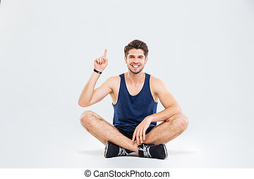 Cheerful man athlete sitting with legs crossed and pointing...