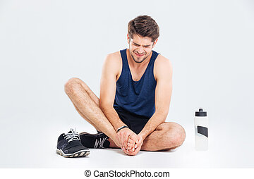 Fitness man sitting and suffering with foot pain over white...