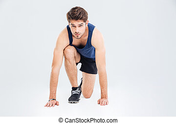 Attractive focused young sportsman ready to start running -...