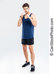 Muscular male fighter standing isolated