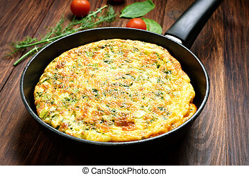 Omelette in frying pan on wooden table