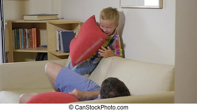 Son and dad fighting with pillows at home