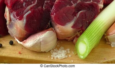 Raw beef on wooden board with garlic and onions