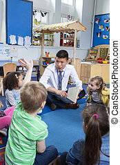 Storytime at Nursery - children are being read a story in...