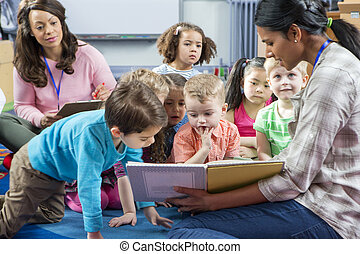 Storytime at Nursery - Female teacher giving a lesson to...
