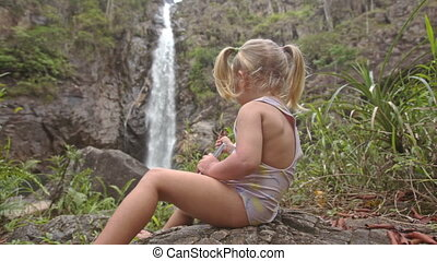 Closeup Little Girl Photos with Phone on Stone at Waterfall...