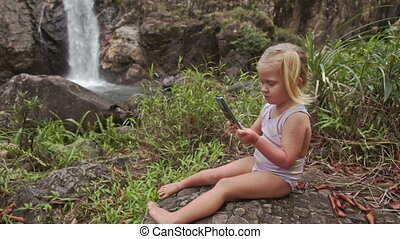 Closeup Little Girl Makes Selfie with Phone at Waterfall -...