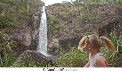 Closeup Little Girl Plays on Stone against Waterfall Cascade...