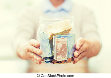 close up of senior woman with money in glass jar - savings,...