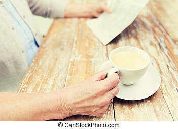 senior woman with coffee reading newspaper at home - age,...