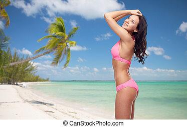 happy woman in pink bikini swimsuit on beach - people,...