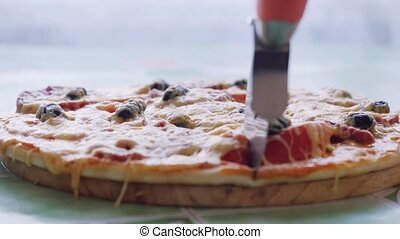 Pizza on dish wooden board Hand cutting with pizza cutter...