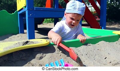 a child plays in the sandbox with a shovel