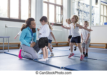 Nursery P.E lesson - Nursery teacher reassuring one of her...