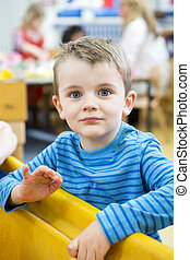 Playing in the Sand Pit - Portrait of a little boy who is...