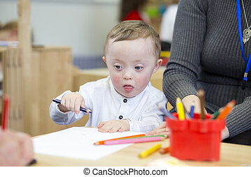 Colouring in at nursery - Down Syndrome child doing...