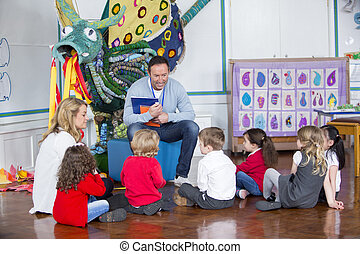 Storytime at Nursery - Small group of nursery children are...