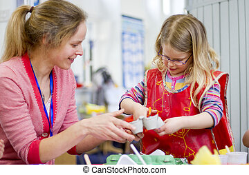 Teacher Helping in Arts and Crafts - Nursery teacher helping...