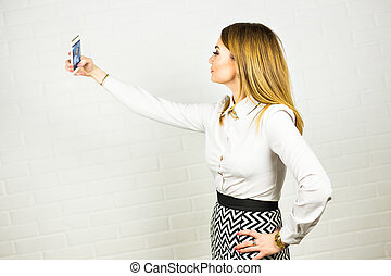Young woman taking a selfie inside office.