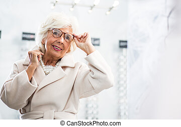 Elegant grandma having her glasses fitted - Fancy old woman...