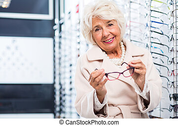Elegant glasses for an elegant lady - Elegant senior lady at...