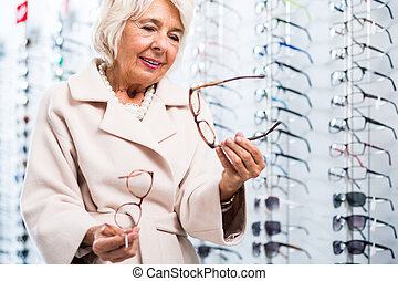 Keeps on changing her mind - Elegant old woman at the...