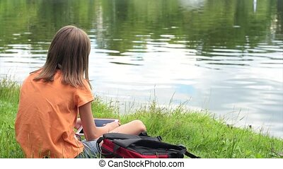 Little girl at lakeside - Little girl with tablet pc at...