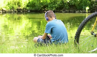 Teen boy at lakeside - Teen boy with tablet pc and...