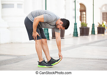 Man stretching before working out outdoors - Profile view of...