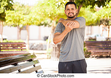Young man stretching his arms before working out - Portrait...