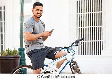 Attractive cyclist using a smartphone - Portrait of a...