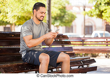 Male runner using a smartphone at the park - Handsome young...