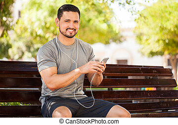 Latin young man listening to music in a park - Portrait of...