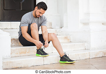Male runner tying his shoes - Handsome young man with a...