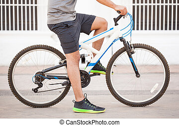 Closeup of a man riding a bike - Profile view of a young fit...