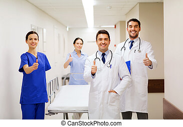 happy doctors showing thumbs up at hospital - clinic,...