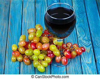 Red wine in glass and bunch of grapes on wooden table